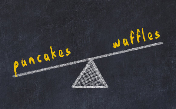 Chalk board sketch of scales. Concept of balance between pancakes and waffles