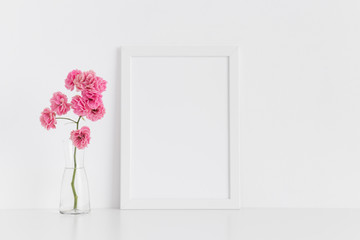 White frame mockup with pink roses in a glass vase on a white table.Portrait orientation.