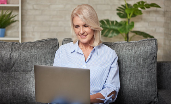 Senior woman is working on her laptop computer sitting on a sofa at home