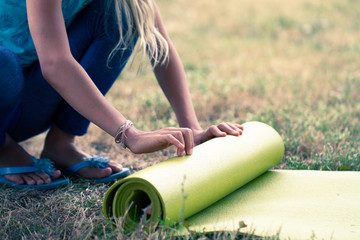 Cropped image of girl rolling yoga mat. Close-up of attractive young woman folding green yoga or fitness mat after working out in a glade in the woods or a city Park . Healthy life