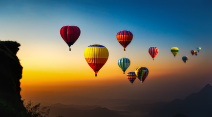 Poster Ballon Hot air balloons flying over the sunrise mountain at phucheefa mountain. Chiang Rai Province, Thailand