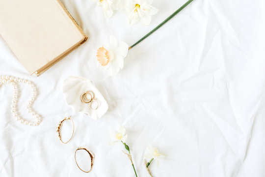 Minimal fashion French style composition with women's accessories: earrings, necklace, rings on white linen. Flat lay, top view.