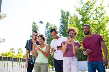 Happy friends watching content on phones and having fun. Group of men and women standing together, using smartphones and showing screens to each other. Communication or leisure concept