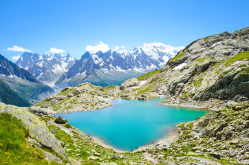 Beautiful landscape of French Alps. Turquoise Lake Blanc, in French Lac Blanc photographed on a sunny summer day with Mount Blanc and other high Alpine mountains in background. Amazing nature, France
