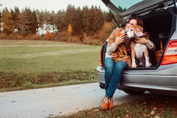 Woman with dog sit together in cat truck and warms цшер hot tea. Auto travel with pets concept image.