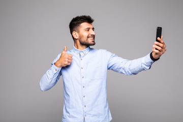 Portrait of friendly creative man with cell smart phone in hand shooting selfie on front camera gesturing thumbs up isolated on grey background