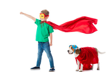 full length view of smiling preschooler child with fist up and beagle dog in masks and red hero cloacks isolated on white