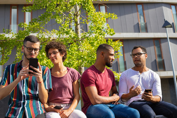 Happy peaceful people with phones sitting on parapet outside. Men and woman using smartphone, watching content and chatting. Leisure concept