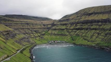 Wall Mural - Flight over a bay towards the small village of Tjornuvik on Faroe Islands