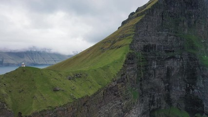 Wall Mural - Flight away from a huge cliff with a small lighthouse on Kalsoy, Faroe Islands