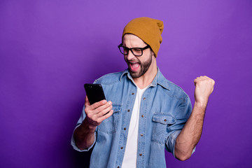 Cool handsome guy holding telephone watch football match casual denim outfit isolated violet background
