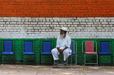 A Muslim man sits on a chair on a roadside pavement in New Delhi