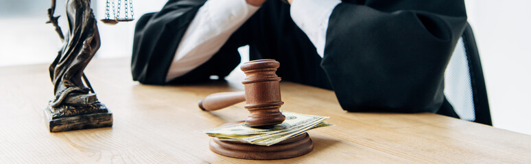 selective focus of wooden gavel with money near judge in glasses and statuette of justice Wall mural