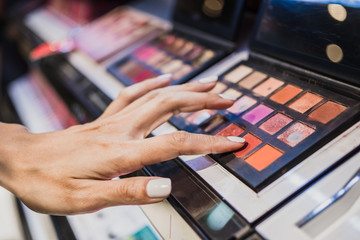 Hand of woman touching colorful cosmetic powder for make up