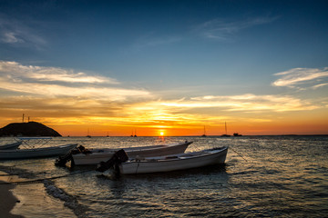Boats anchored with a beatiful sunset at the background. Los Roques National Park, Venezuela