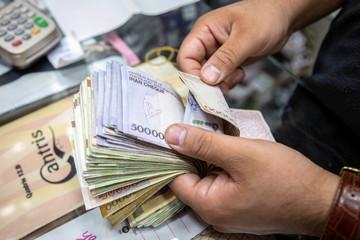 A salesman counts money in Tajrish Bazaar, Tehran