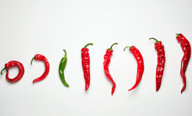 In de dag Hot chili peppers whole ripe red hot chili peppers on a white background, one green