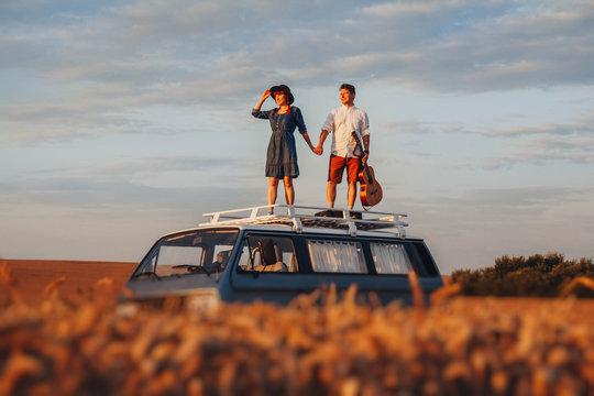 Young couple man with a guitar and woman in a hat are standing on the roof of a car in a wheat field. Travel and adventur