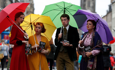 Performers hand out flyers on the The Royal Mile trying to attract people to their show, in Edinburgh