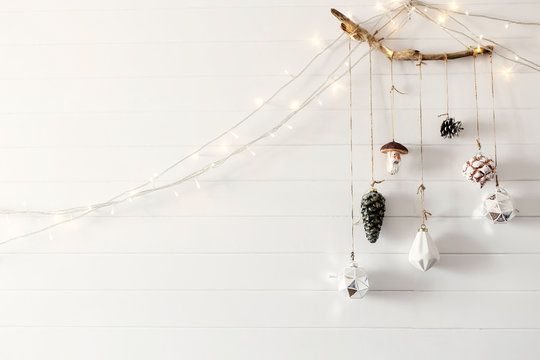 Christmas vintage toys hanging on wooden branch on white wall with festive lights in modern room, scandinavian minimal style. Stylish glass ornaments, holiday decorations. Space for text