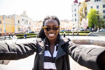 Pretty african woman taking a selfie in modern city