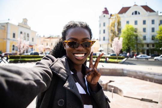 Young pretty african woman take selfie on the sunny city street