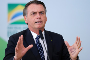 A handwritten note is seen on the hand of Brazil's President Jair Bolsonaro during a ceremony to launch the program 'Doctors in Brazil' at the Planalto Palace in Brasilia