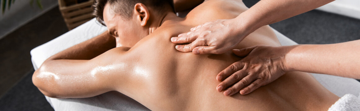 panoramic shot of masseur and shirtless man lying on massage table
