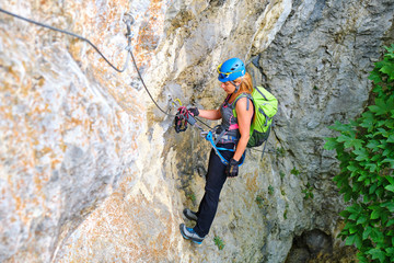 Female tourist with climbing gear and backpack resting on a via ferrata route, hanging from a locking carabiner attached to her via ferrata set from the loop designated for pausing.