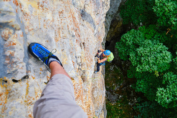 Woman tourist climbing a vertical, difficult via ferrata section in Baia de Fier, Romania, on a route called Dragons Amphitheater (Amfiteatrul Zmeilor), rated D. Point of view from above.