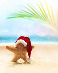Starfish in Santa hat on the summer beach. Christmas concept