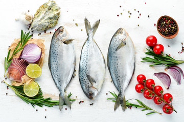Raw fish with lemon, salt and rosemary. On a white wooden background. Top view. Free copy space.