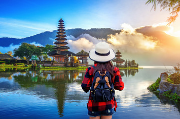 Woman traveler with backpack looking to pura ulun danu bratan temple in Bali, indonesia.