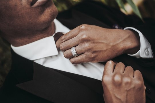 Closeup of an African-American male wearing a ring and a black suit jacket fixing his necktie