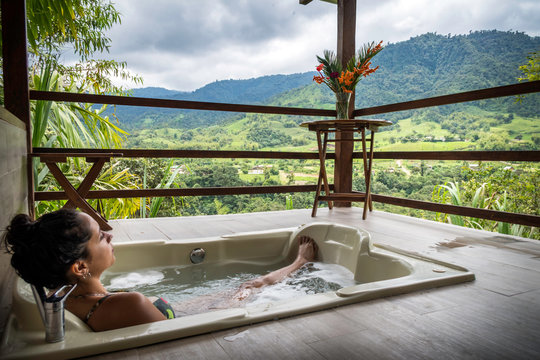 relaxed woman inside a bathtub with water on the balcony of a hotel with mountain view (or also called sierra) The construction is made of wood
