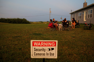 A sign announcing the use of security cameras is displayed in Jim and Kim Mahoney's yard in Mt. Pleasant