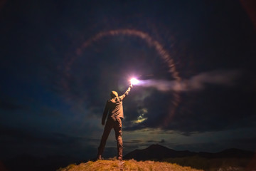 The male with a bright firework stick standing on a mountain. evening night time Fototapete