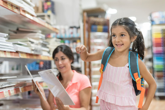 mother and daughter in store choosing material for back to school