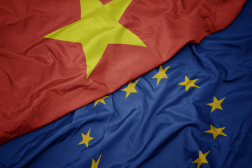 waving colorful flag of european union and flag of vietnam.