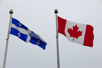 flags of canada and quebec waving in the wind in front of white