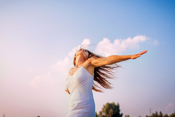 Young woman feeling free and happy raising arms and spinning around outdoors at sunset
