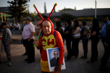"""Jose Luis Duran waits dressed as the popular Mexican character known as """"El Chapulin Colorado"""" for the opening parade of the festivities of El Divino Salvador del Mundo (The Divine Savior of The World), patron saint of the capital city of"""