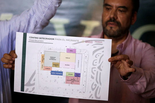 A man displays a floor plan during a media tour to show the facilities a newly renovated migrants' shelter in Ciudad Juarez