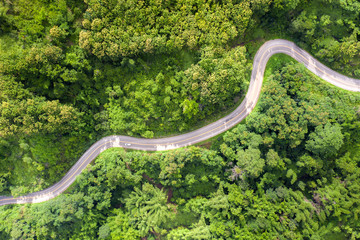 Spoed Fotobehang Luchtfoto Aerial view over mountain road going through tropical rainforest landscape in Thailand..