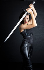 Woman in urban fantasy costumes holding weapons