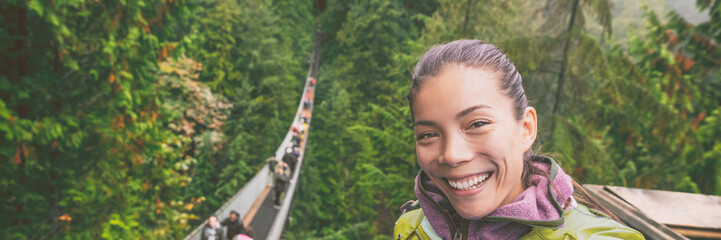 Wall Mural - Canada travel tourist woman taking selfie photo at Capilano Suspension Bridge in Vancouver, British Columbia, canadian vacation destination for tourist. Asian girl talking to camera phone.