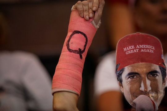 A supporter of U.S. President Donald Trump holds up her cast with a letter Q on it, and a face mask during a campaign rally for the president in Cincinnati