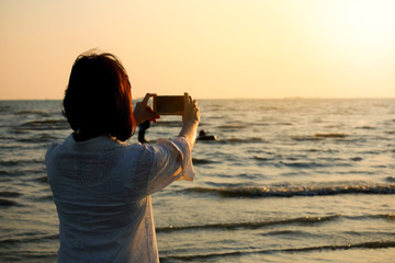 woman  take pictures of the Beach and sea. Sunrise time recording photo phone.Travel concepts and technology