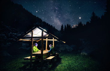 Tourists relaxing under starry sky in mountain landscape