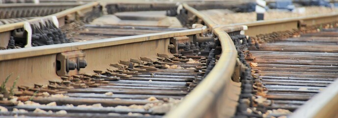 Railroad rails at a small station, fork, arrows, mechanical elements, wide view.